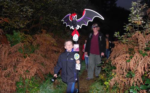 Child holds aloft glowing bat model