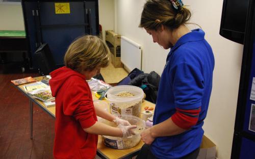Child with UHP West Area Warden making bird feeder
