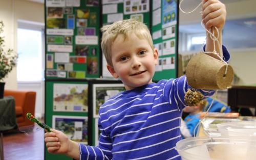 Child holding up home made bird feeder